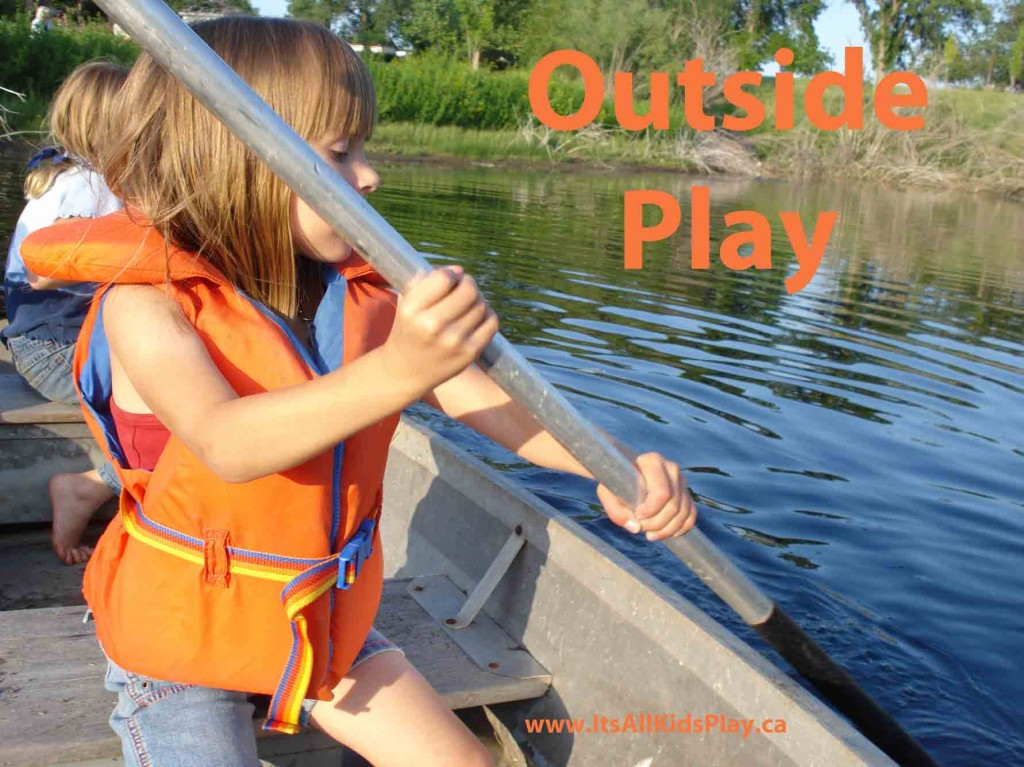 Outside Play. Kids paddling a boat in a pond.
