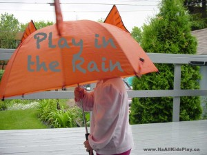 Play in the rain. Child under an umbrella.